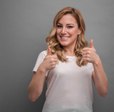 Blonde woman on gray background shows thumbs up.