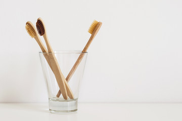 set of natural toothbrushes in glass on table in bathroom © colnihko
