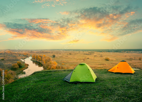 canvas print picture Green and orange tent on riverbank on sunny summer day