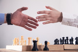 Business people shaking hands. Playing chess game
