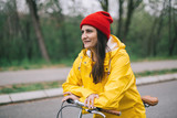 Woman in yellow raincoat posing with bicycle on rain day