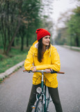 Woman in raincoat pose with bicycle in the park