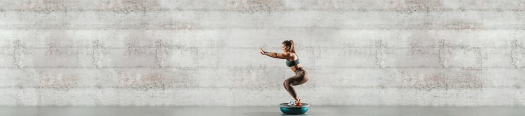 Side view of sporty woman doing exercises on bosu ball. In background gray wall, copy space.