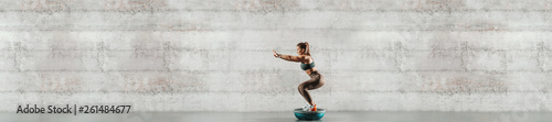 Leinwanddruck Bild Side view of sporty woman doing exercises on bosu ball. In background gray wall, copy space.
