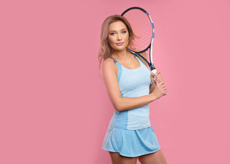 Beautiful young girl tennis player on pink background with tennis racket