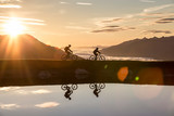 Two mountain bikers at a mountain lake in the Alps at sunrise.
