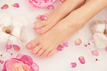 Woman is taking bath. Close up of female feet and hands in bath full of water and flowers. © forma82
