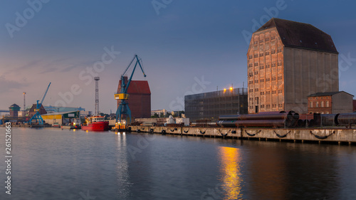 Leinwanddruck Bild The port of Stralsund with docks, warehouses and cranes and part of the Rügen bridge