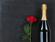 Anniversary background with single red rose and champagne on natural black slate stone