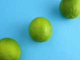 Thre isolated Limes on a Pastel blue bakcground