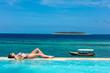 Leinwandbild Motiv one caucasian woman enjoying vacations  sunbathing on a infinity swimming pool by the seaside looking at the idian ocean Muyuni  in Unguja aka Zanzibar Island Tanzania East Africa