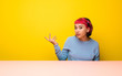 Young woman with pink hair making doubts gesture