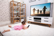 Little Girl Lying On Carpet Watching Television - 261575040