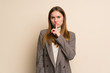 Young business woman showing a sign of silence gesture putting finger in mouth