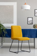 Yellow chair with metal legs placed by the table with blue tablecloth in real photo of light grey living room interior with fresh plants, lamp and posters on wall