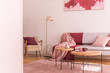 Quadro Lamp between armchair and sofa with pink and red blanket in flat interior with tables. Real photo