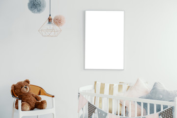 Mockup of empty white poster above cradle in baby's bedroom interior with toy on chair. Real photo