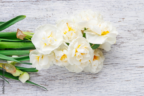 White narcissus flowers on wooden background.