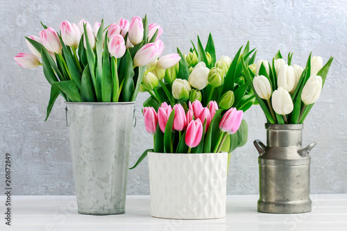 Tulip bouquets on white wooden table.
