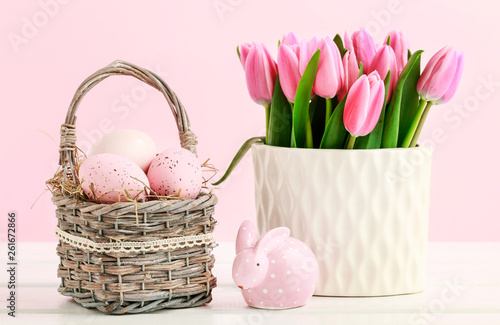 Pink Easter decorations: tulip flowers, basket with painted eggs and dotted rabbit figure