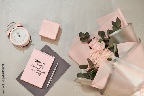 Gift box, alarm clock and pink rose flowers on white table top view in flat lay style. Greeting card for Mother or Woman day.