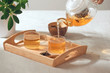 A hand pouring tea from glass teapot on wooden serving tray