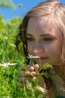 canvas print picture - Eine junge Frau riecht an einer Blume auf einer Wiese