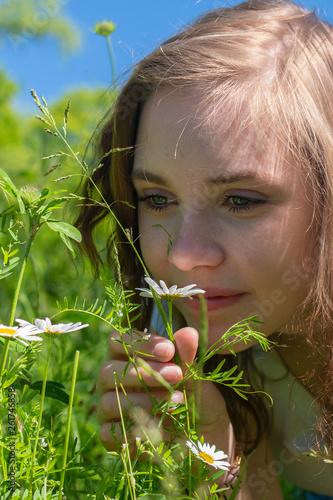 canvas print picture Eine junge Frau riecht an einer Blume auf einer Wiese
