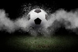Traditional soccer ball on soccer field. Close up view of soccer ball (football) on green grass with dark toned foggy background