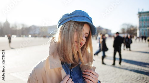Stylish young blonde in denim cap and beige raincoat. Beautiful young woman