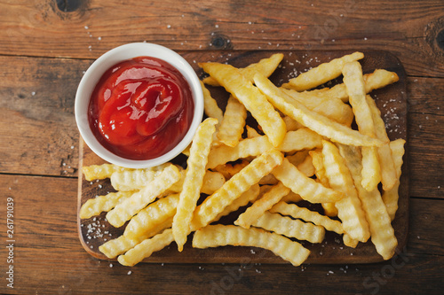 French fries with ketchup on wooden board © Nitr