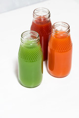 colorful vegetable juices in bottles on white table, vertical top view