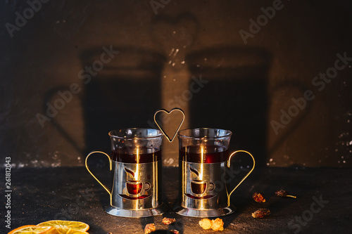 Two cups of fruit tea and a shape in the form of a heart, with a shadow on the wall. Concept for the day of lovers on a dark background © Татьяна Скорина