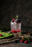 Refreshing summer drink with syrup, raspberry, blackberry and ice on dark background, Glass with cold and healthy beverage