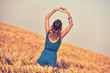canvas print picture - Girl holding heart-shape symbol for love in a wheat field.