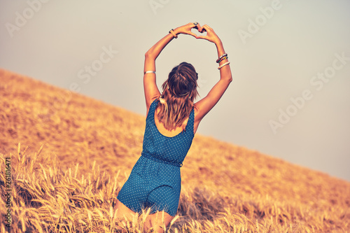 canvas print picture Girl holding heart-shape symbol for love in a wheat field.