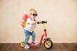 Leinwandbild Motiv Happy child playing with toy rocket at home