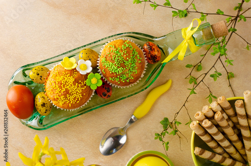 Muffins decorated with sprinkles, flowers of mastic, colored easter quail eggs on a kitchen table. Top view. Happy Easter holiday and greeting card concept. © tychynska