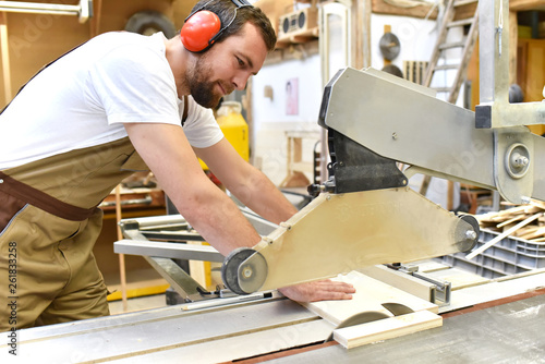 friendly carpenter with ear protectors and working clothes working on a saw in the workshop - 261833258