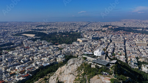 Aerial drone panoramic photo of iconic Saint George Lycabettus chapel as seen from top of hill, all Athens cityscape and Acropolis hill at the background, Athens historic centre, Attica, Greece © aerial-drone
