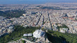 Aerial drone panoramic photo of iconic Saint George Lycabettus chapel as seen from top of hill, all Athens cityscape and Acropolis hill at the background, Athens historic centre, Attica, Greece