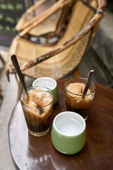 Refreshing iced coffee drinks and cups with water on round table outdoors