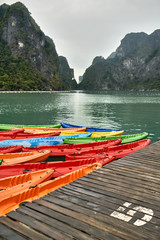 Multicolored canoes moored to wooden pier on nature background