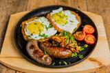 Tradycyjne placki ziemniaczane ze smażonymi jajkami, pieczarkami, kiełbaskami i pomidorami podawane na gorącej patelni.