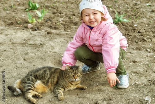 Little baby girl with street cat