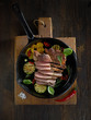 Sliced grilled  barbecue steak in a pan on a wooden background - 261912440