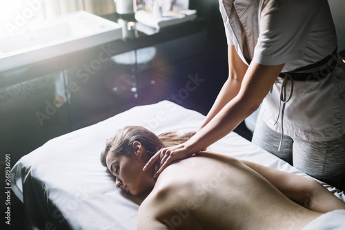 canvas print picture Masseur doing massage on woman body in the spa salon. Beauty treatment concept.