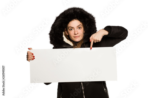 canvas print picture Young model in winter jacket with hood shows an empty advertising board on white background