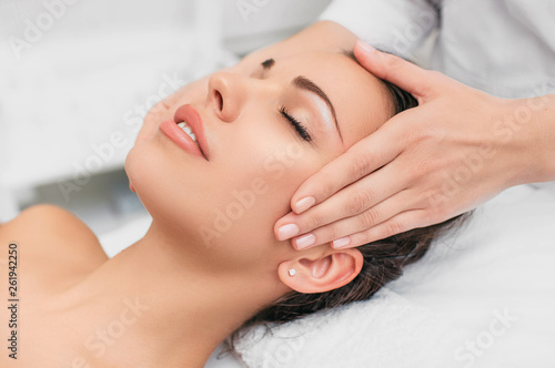 Beautiful woman enjoying in head massage during beauty treatment in the spa. © Erica Smit