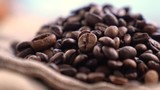 Black Coffee Grains. Black coffee is laid out on a bag spinning on a stand around its axis.